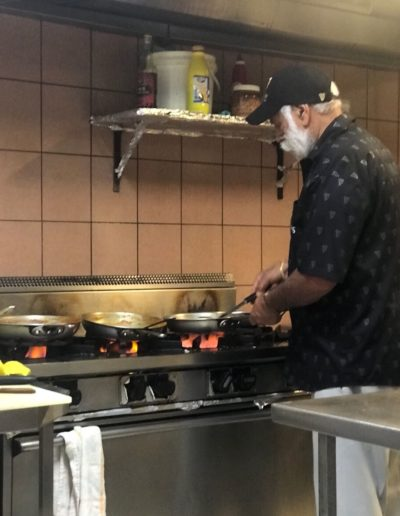 Mick Hundal cooking food in the back of a restaurant